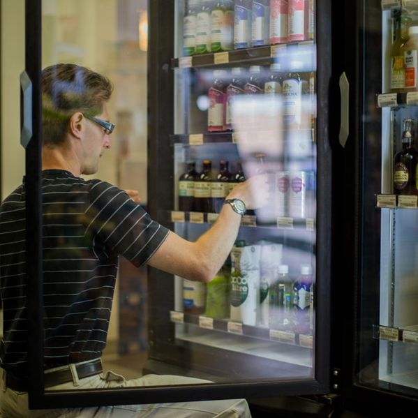 Customer picking a drink from a fridge